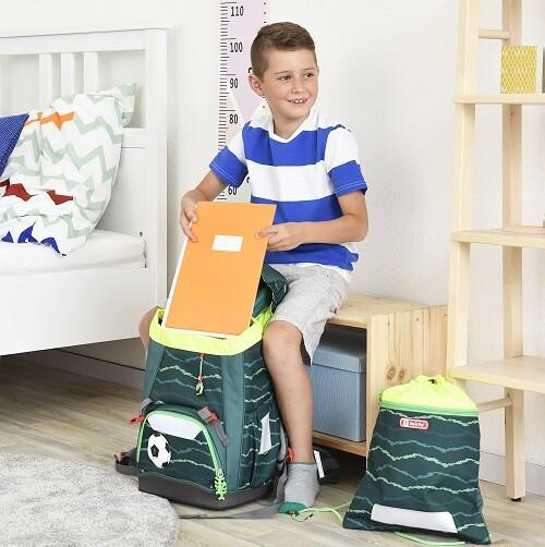 Junge packt Hefte in seinen Schulranzen