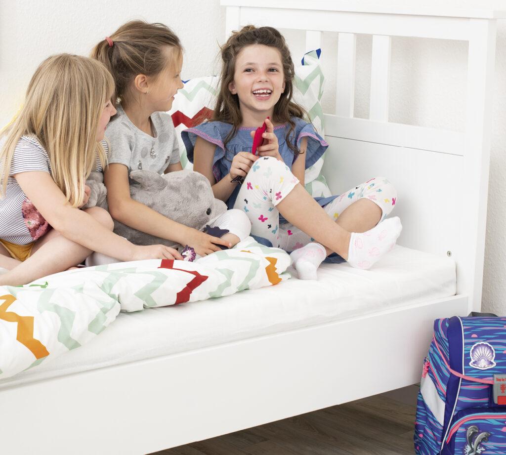 Mädchen sitzen im Bett und spielen mit MAGIC MAGS