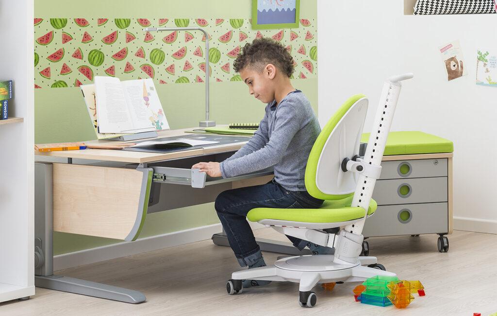 Kind sitzt an ergnomischen Schreibtisch