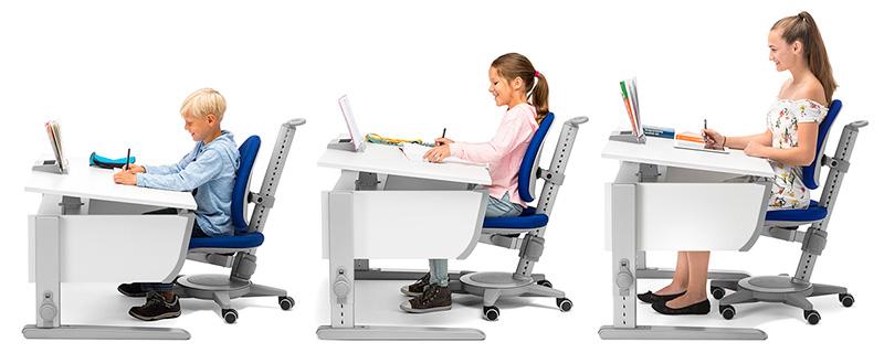 Drei unterschiedlich große Kinder sitzen an einem Schreibtisch, dessen Höhe jeweils angepasst ist