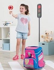 Mädchen steht an einem selbst gebastelten Zebrastreifen im Kinderzimmer und hält eine Polizeikelle hoch, daneben steht der SPACE NEON