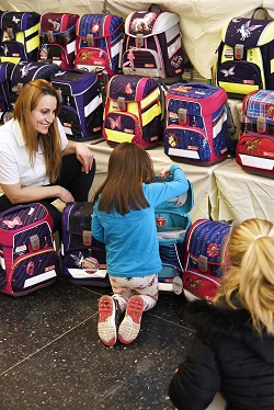Mutter und Kind werden auf einer Schulranzenparty von einer Fachverkäuferin beraten