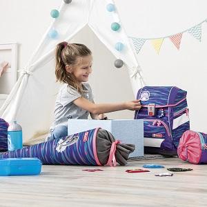 Mädchen betrachtet ihren Schulranzen, um sie herum liegen Schultüte, Trinkflasche und Lunchbox passend zum Schulranzen