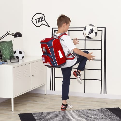Junge spielt Fußball, er trägt den FC Bayern Schulranzen von Step by Step