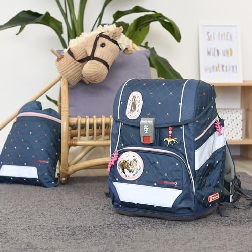 Schulranzen 2IN1 PLUS Spiegelburg im Pferdefreunde-Motiv steht im Kinderzimmer, daneben steht ein Steckenpferd