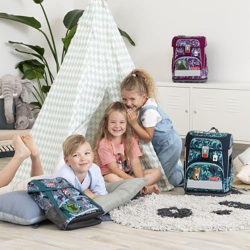 Drei Kinder sitzen in einem Tipi-Zelt, um das Zelt stehen die verschiedenen WWF Schulranzen und Rucksäcke