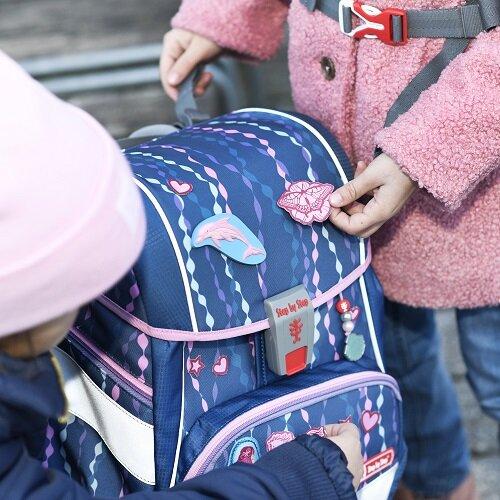 Mädchen kleben reflektierende Sticker auf ihren Step by Step Schulranzen.