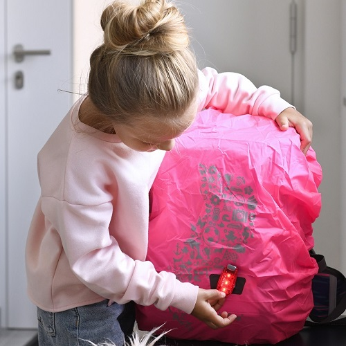 Mädchen befestigt LED-Klemmleuchte an ihrem Schulranzen mit Neon Pull-Over.