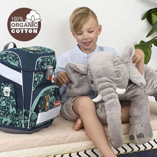 Junge spielt mit riesigem Kuscheltier-Elefant. Daneben steht sein Step by Step Schulranzen aus Bio-Baumwolle.