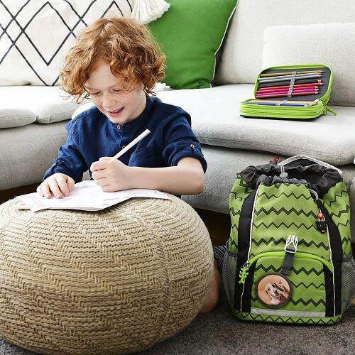 Junge malt Motiv, dass er anschließend an seinem KID-Rucksack anbringt
