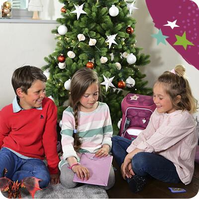 Kinder sitzen unter dem Weihnachtsbaum und packen Geschenk aus